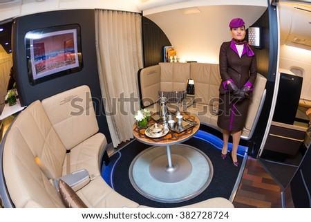 Dubai, UAE - NOVEMBER 09, 2015: Etihad Airways Airbus A380 cabin crew member. Airbus A380 upper deck lounge. Business class travel.  Etihad Airways Airbus A380 The Lobby on November 09, 2015 in Dubai - stock photo