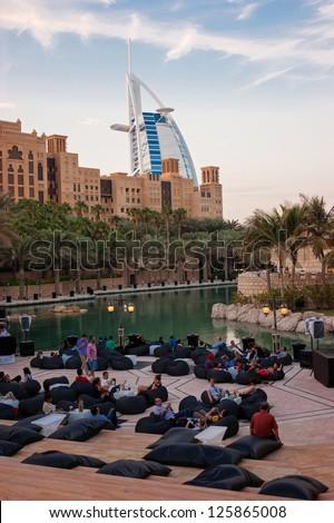DUBAI, UAE-NOVEMBER 15: Evening view of Burj al Arab hotel (7 star, 1999) from territory of Madinat Jumeirah hotel on November 15, 2012 in Dubai, UAE. Madinat Jumeirah - luxury 5 star hotel - stock photo