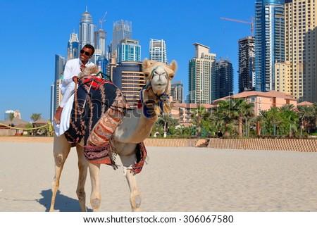 DUBAI, UAE - NOVEMBER 11, 2013: High rise buildings and man riding a camel on the beach - stock photo