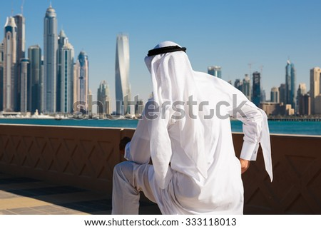 DUBAI, UAE - NOVEMBER 7, 2013: Modern buildings in Dubai Marina. Man in Arab dress looks at the city