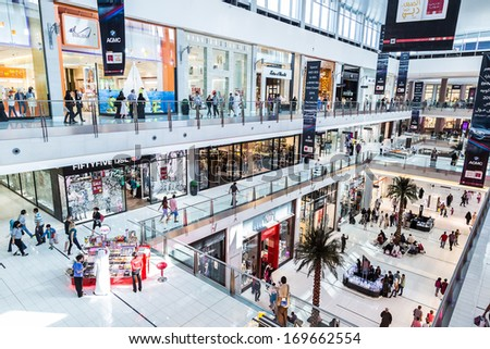 DUBAI, UAE - NOVEMBER 14: Shoppers at Dubai Mall on November 14, 2012 in Dubai. At over 12 million sq ft, it is the world's largest shopping mall  - stock photo