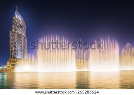 DUBAI, UAE - NOVEMBER 25, 2014: The Dancing Fountain of Dubai performs to the beat of the selected music at dusk near Burj Khalifa and  Dubai Mall in downtown of Dubai. Located on Sheikh Zayed Road. - stock photo