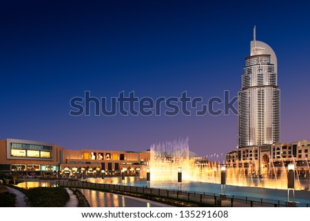 DUBAI, UAE - OCT 10: The Dancing Fountain of Dubai performs to the beat of the selected music at dusk on Oct 10, 2010 in Dubai, UAE. The fountain is overlooked by Dubai Mall and the Address Hotels - stock photo