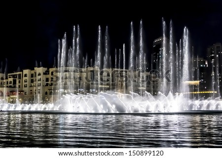DUBAI, UAE - OCTOBER 1: A record-setting fountain system set on Burj Khalifa Lake - 6600 lights and 25 projectors, it shoots water 150 m into the air, at October 1, 2012 in Dubai, United Arab Emirate. - stock photo