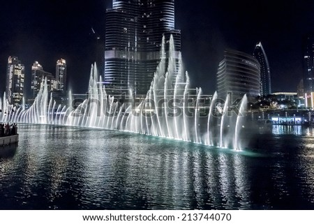 DUBAI, UAE - OCTOBER 1, 2012: Dubai Fountain is world largest choreographed fountain system set on Burj Khalifa Lake - 6600 lights and 25 colored projectors, it shoots water 152 m into the air. - stock photo