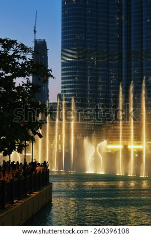 DUBAI, UAE - OCTOBER 31, 2013: Fountain in the lake near Dubai Mall. Lake - 6600 lights and 25 projectors, it shoots water 150 m into the air.  - stock photo