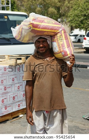 DUBAI, UAE - OCTOBER 11: Portrait of an unknown docker with bale in Port Said Dubai; UAE on October 11, 2011.