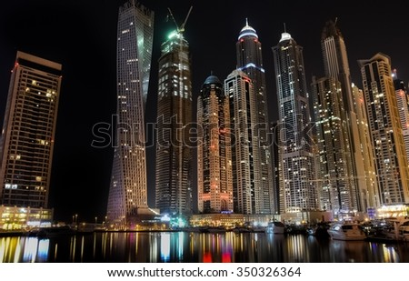 DUBAI, UAE - October 21, 2015 : Skyscrapers in Dubai Marina during night. Long Exposure shot covering Famous Cayan Tower, Princess tower, Torch Tower and buildings surrounding them. - stock photo