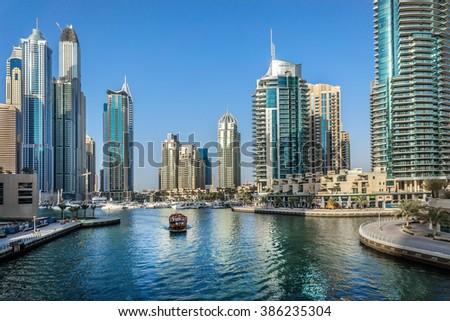 DUBAI, UAE - SEPTEMBER 8, 2015: Boat and modern skyscrapers in Dubai Marina. Marina - artificial canal city, carved along a 3 km stretch of Persian Gulf shoreline. - stock photo