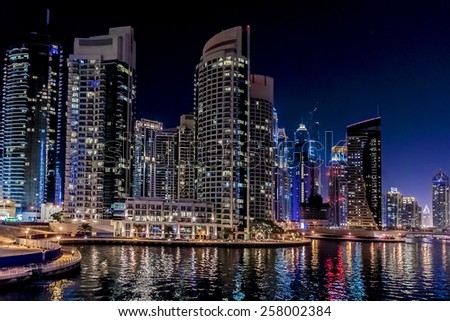 DUBAI, UAE - SEPTEMBER 29, 2012: Night view at modern skyscrapers in Dubai Marina. Marina - artificial canal city, carved along a 3 km stretch of Persian Gulf shoreline. Dubai, United Arab Emirates. - stock photo