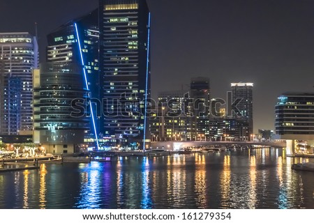 DUBAI, UAE - SEPTEMBER 29: Night view at modern skyscrapers in Dubai Marina on September 29, 2012 in Dubai, UAE. Marina - artificial canal city, carved along a 3 km stretch of Persian Gulf shoreline. - stock photo