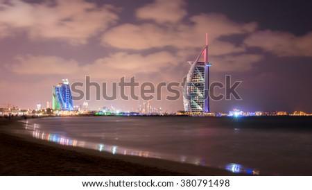 Dubai, United Arab Emirates - Dec 2, 2014 : The illuminated Burj Al Arab and Jumeirah Hotel at the sunset from the Jumeirah beach. Burj Al Arab is a luxury 7 stars hotel built on an artificial island. - stock photo