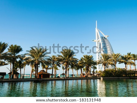 "DUBAI, UNITED ARAB EMIRATES - DECEMBER, 10, 2013: Beach with palms and view on seven stars luxury hotel Burj Al Arab ""Tower of the Arabs"" in Dubai - stock photo"