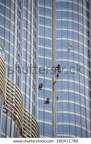 DUBAI, UNITED ARAB EMIRATES-FEBRUARY 7, 2014; Group of workers cleaning windows of the Burj Khalifa in Dubai. February 7, 2014 Dubai - stock photo