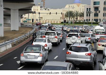 DUBAI, UNITED ARAB EMIRATES - FEBRUARY 9, 2014: Traffic on highway leading to the city center. At rush hour main roads are full with traffic. February 9, 2014 Dubai, United Arab Emirates    - stock photo