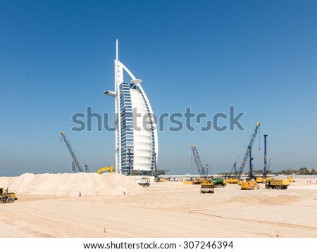 DUBAI, UNITED ARAB EMIRATES - JAN 25, 2014: Cranes and work in progress on construction site near Burj al Arab Hotel, Jumeirah Beach in the city of Dubai, United Arab Emirates - stock photo