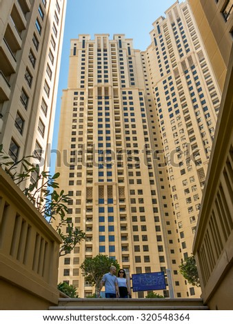 DUBAI, UNITED ARAB EMIRATES - JAN 25, 2014: People walking and highrise buildings The Walk in the Marina district of Dubai, United Arab Emirates - stock photo