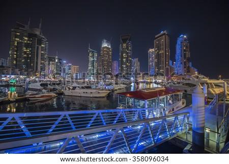 Dubai, United Arab Emirates - January 1, 2016: Modern skyscrapers and water channel with boats of Dubai Marina at sunset, United Arab Emirates - stock photo
