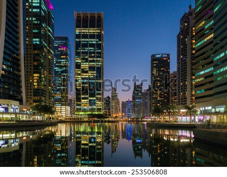 DUBAI, UNITED ARAB EMIRATES - 20 OCTOBER, 2014: Jumeirah Lake Towers in Dubai, UAE. Glittering lights and tallest skyscrapers during a clear evening with blue sky.  - stock photo
