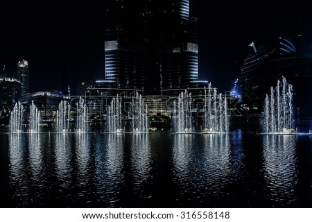 DUBAI, UNITED ARAB EMIRATES - SEPTEMBER 8, 2015: A record-setting fountain system set on Burj Khalifa Lake - 6600 lights and 25 projectors, it shoots water 150 m into the air. UAE. - stock photo