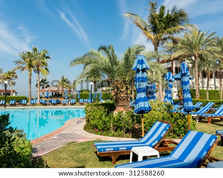 DUBAI, UNITED ARAB EMIRATES (UAE) - JAN 28, 2014: Sunbeds, palm trees and pool in tropical garden of luxury hotel beach resort - stock photo
