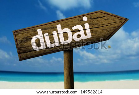 Dubai wooden sign with a beach on background  - stock photo