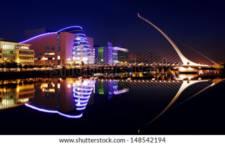 DUBLIN, IRELAND - JULY 22: Barrel shaped Dublin Convention Center (The CCD) and Samuel Beckett Bridge by architect Santiago Calatrava reflecting in the river Liffey on July 22, 2013 in Dublin, Ireland - stock photo