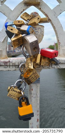 DUBLIN, IRELAND - JUNE 26: Love Padlocks inscribed with names attached to the railings of Dublin city's historic Ha'penny Bridge on June 26, 2014 in Dublin, Ireland. - stock photo