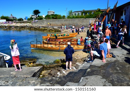 DUBLIN, IRELAND - JUNE 9: Unidentified competitors and onlookers at The East Coast Rowing Council Races on June 9, 2013 in Sandycove, Ireland. Wooden racing skiffs lie along the shoreline. - stock photo