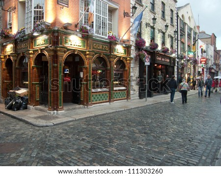 DUBLIN - JUL 27: Unidentified people walk by many bars and pubs in famous Temple Bar quarter on Jul 27, 2009 in Dublin, Ireland. Temple Bar has preserved medieval street pattern, with narrow streets. - stock photo