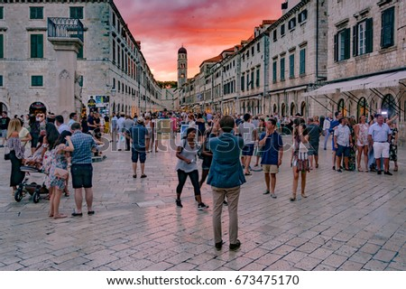 Dubrovnik, Croatia - July 1, 2017: Tourists walk down the famous Stradun, main street in old town of Dubrovnik, during colorful clouds cape above tower of Franciscan monastery on July 1, 2017.