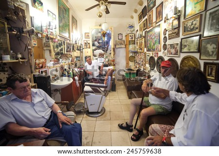 DUBROVNIK, CROATIA - MAY 28, 2014: Hrvoje CIKATO, owner of traditional barber shop Cikato with his customers.  Locals often come for chat and to have drink or two with owner. - stock photo