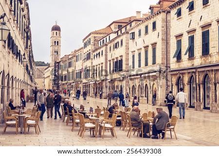 DUBROVNIK, CROATIA - NOVEMBER 20, 2006: People sitting in a bar terrace on Stradun, main street in Dubrovnik, Croatia. Dubrovnik is one of the prominent tourist destinations on the Mediterranean. - stock photo