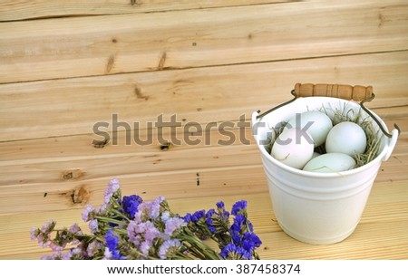 Duck eggs in a ceramic basket decorate with pink and purple flower on the wooden table.Easter festival. - stock photo