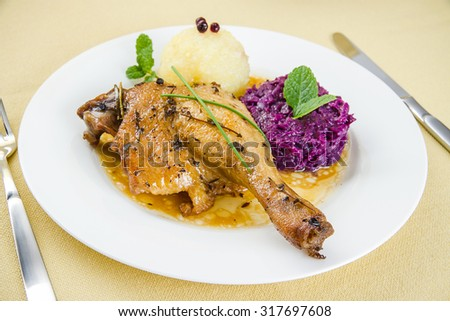 Duck leg, potato dumplings, red cabbage, close up - stock photo