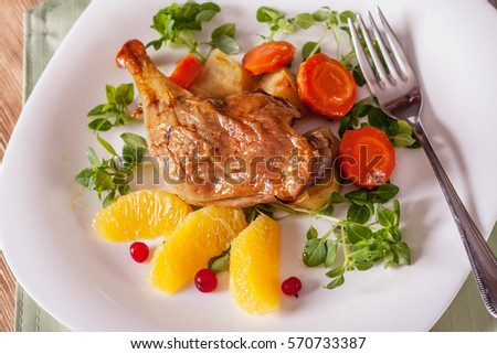 Duck leg roasted with vegetables, oranges and basil Serving