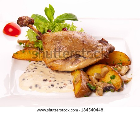 duck leg with potato on white