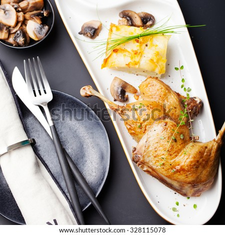Duck legs confit with potato gratin and mushroom sauce . Restaurant serving. - stock photo