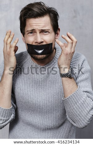 Duct taped man in studio - stock photo