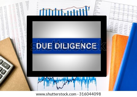 due diligence word on tablet with financial graph background - stock photo
