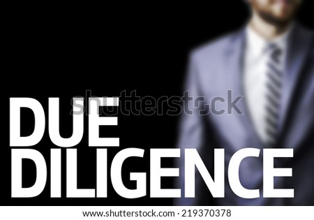 Due Diligence written on a board with a business man on background - stock photo