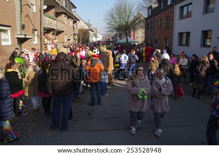 DUISBURG, GERMANY - 15.02.2015 An unidentified woman and man in the annual carnival costumes & masks are on the road. They give sweets to children and adults, play a musical instrument, having fun.