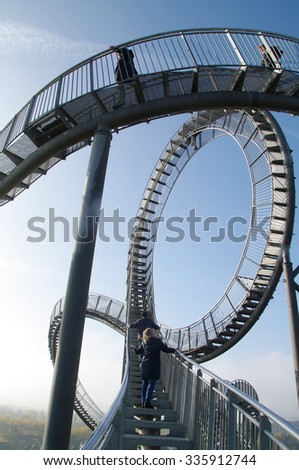 DUISBURG, GERMANY - 01 November 2015 Tiger and Turtle sculpture in Anger Park. Roller coaster magic Mountain with visitors