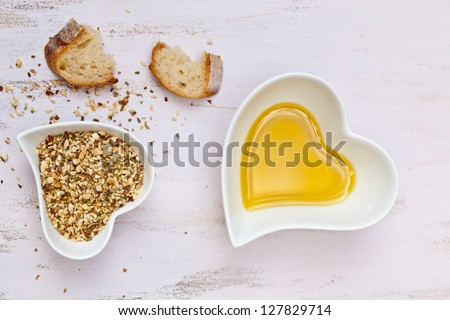 Dukkah with crusted bread and olive oil in heart shaped bowls - stock photo