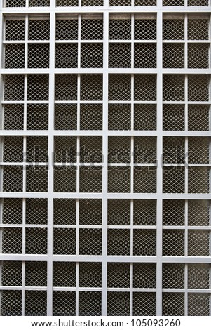 Dull silver color metal bars over screen covering building window - stock photo