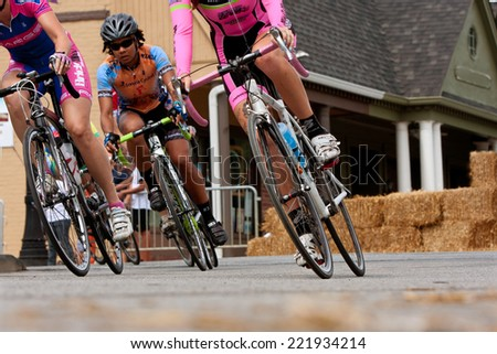DULUTH, GA - AUGUST 2:   Low-angle perspective of a group of female cyclists racing into a turn as they compete in the Georgia Cup Criterium event on August 2, 2014 in Duluth, GA.