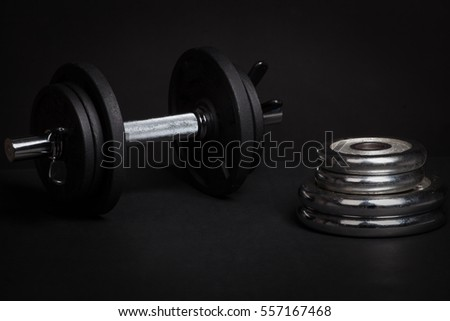 Dumbbell and barbell discs for workout on black background