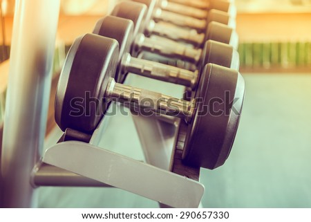 dumbbell in gym - vintage effect and sun flare filter effect - stock photo