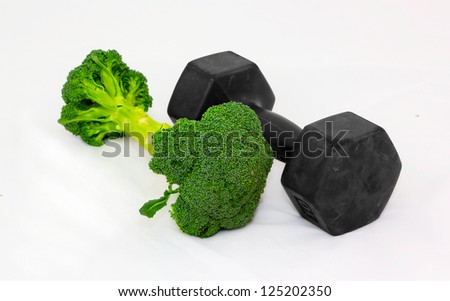 Dumbbell made of Broccoli on white background. Focus in front.