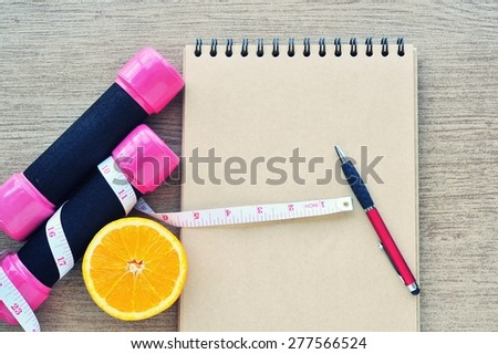 Dumbbell,measuring tape,orange and recording book on tile floor. Planning control diet concept. - stock photo